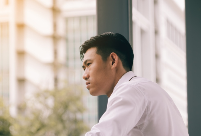 Young man looking anxiously out of window