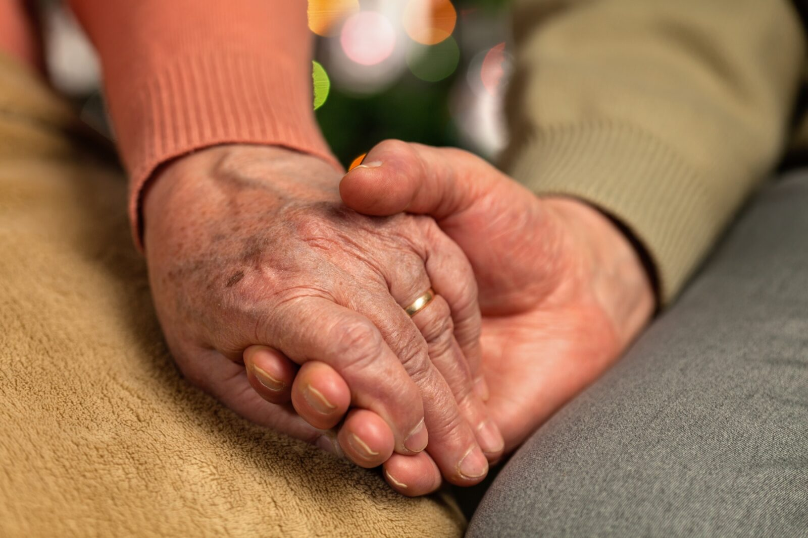 Elderly couple holding hands close up