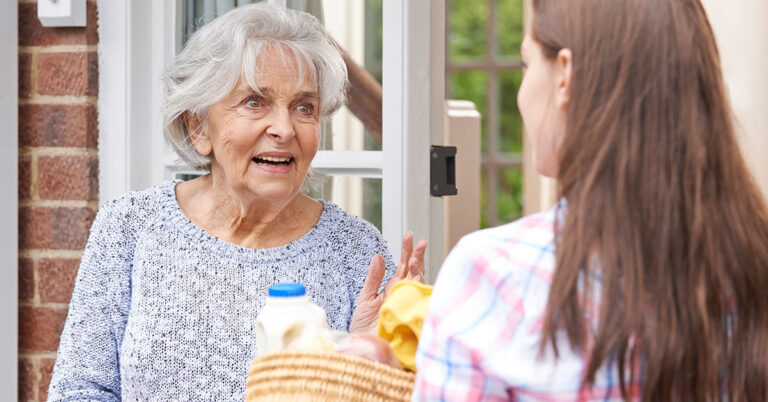 woman volunteering delivering food to an elderly lady