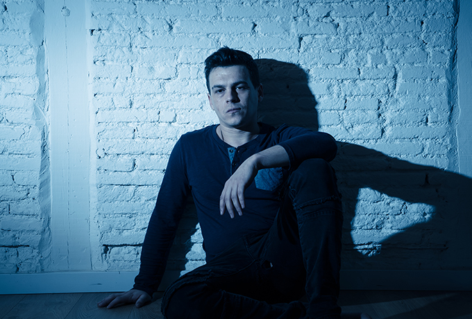 Sad looking man sitting against a wall