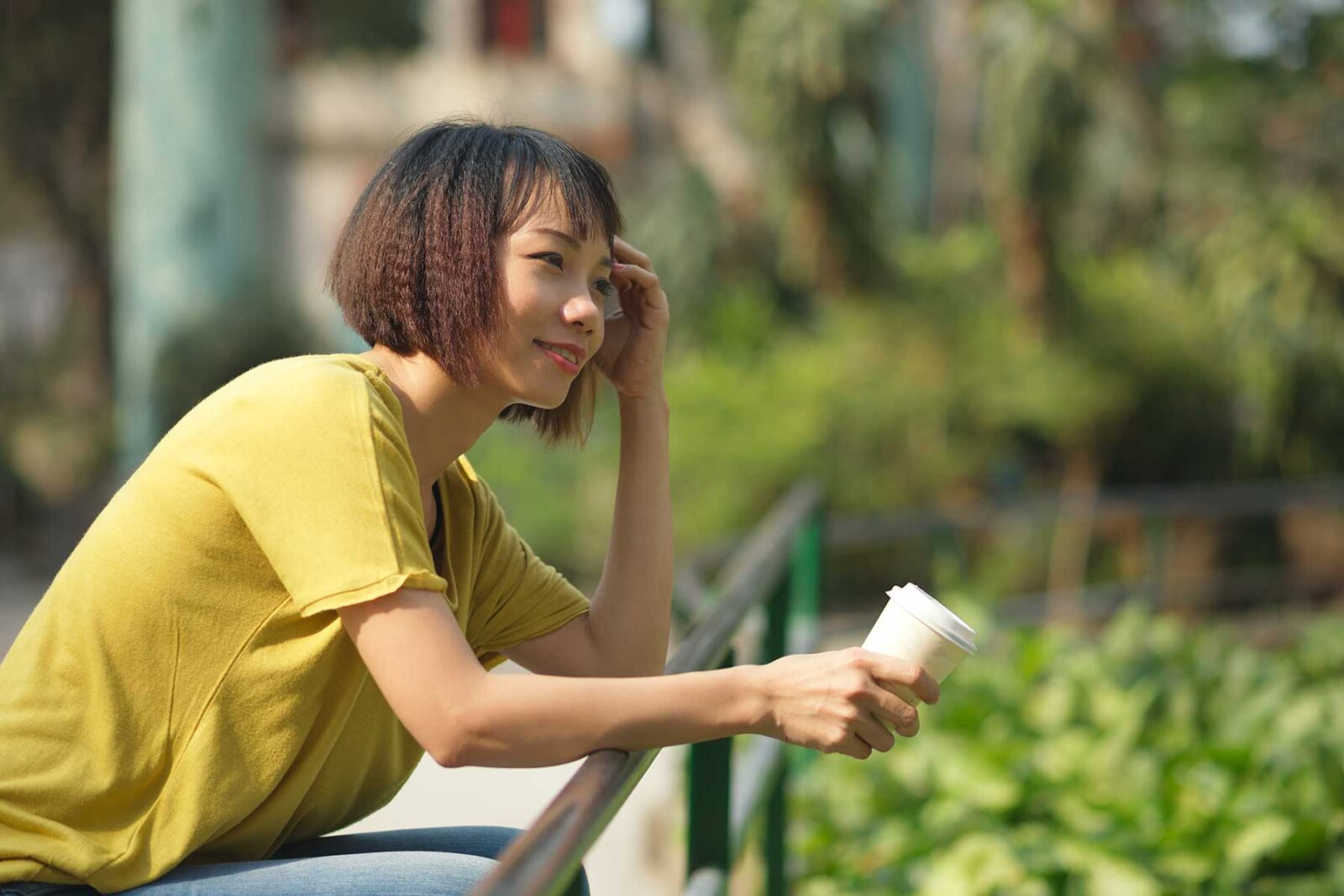 Smiling woman drinking a coffee in a park